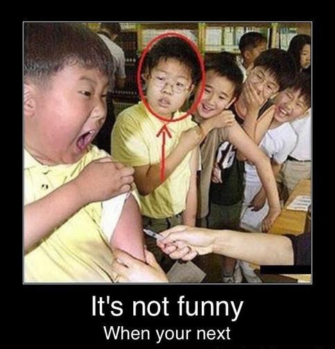 Kinder werden geimpft. Der Junge, der gerade die Spritze in dem Arm bekommt schreit. Alle anderen lachen, nur der nächste Junge schaut ängstlich