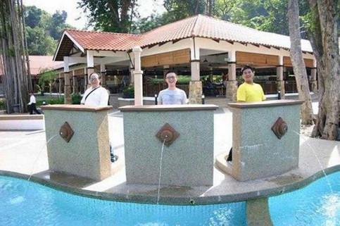Drei Männer stehen an Brunnen, man denkt, sie würden in den Pool pinkeln.