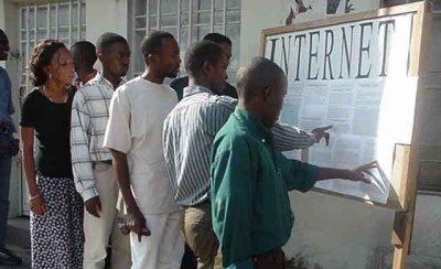 """Ein Brett mit ausgedruckten Zetteln, das mit """"Internet"""" beschriftet ist und vor dem lesende Afrikaner stehen."""