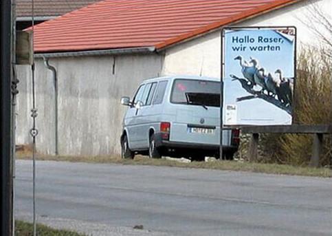 """Ein Schild """"Hallo Raser, wir warten!"""". Hinter dem Schild steht ein Transporter, der wahrscheinlich blitzt."""