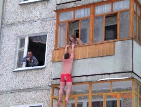 Ein Liebhaber in Unterhose hängt aus einem Fenster, während ein Mann mit einem Gewehr auf ihn zielt.