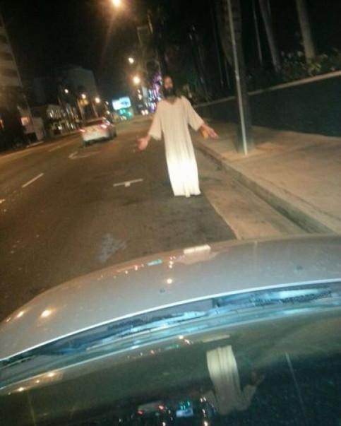 Ein Mann, der wie Jesus aussieht, steht auf einem Parkplatz an einer Straße.