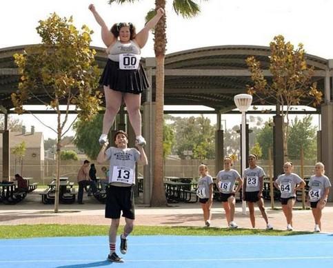 Ein schmächtiger Junge hebt eine dicke Cheerleaderin hoch.