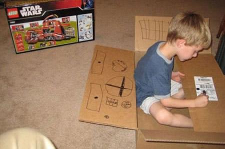 Ein Junge hat ein Lego-Star-Wars-Spiel geschenkt bekommen und spielt lieber mit dem Karton als mit dem eigentlichen Geschenk.