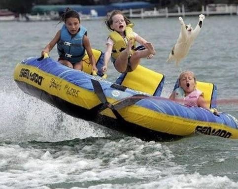 Kinder und eine Katze auf einem gezogenen Gummiboot, Kinder und Katze fliegen durch die Luft.