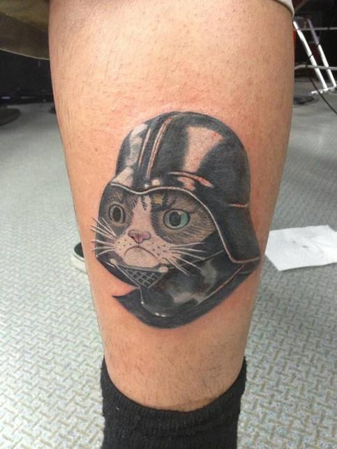 Ein Mann hat auf seinem Unterschenkel eine Katze tätowiert, die einen Darth Vader-Helm trägt.