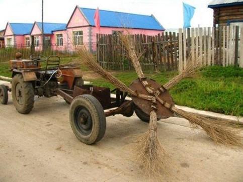 Eine Kehrmaschine, die aus großen Reisigbesen besteht. Diese sind sternförmig auf einer Platte montiert, die von einem alten Traktor gezogen wird.