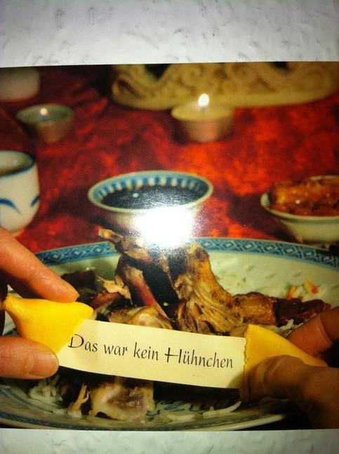 """Ein Gast öffnet seinen Glückskeks in einem chinesischen Restaurant. Auf dem Teller liegen nur noch Knochen. Auf dem Zettel des Glückskekses steht: """"Das war kein Hühnchen""""."""