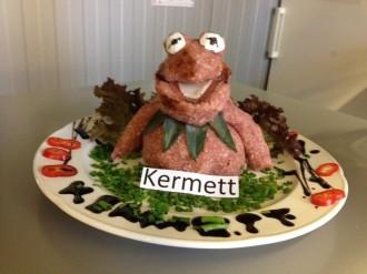 """Auf einem Teller wurde aus rohem Hackfleisch Kermit aus der Sesamstraße geformt und diesem Gericht wurde der Name """"Kermett"""" gegeben, was auf einem Schild zu lesen ist."""