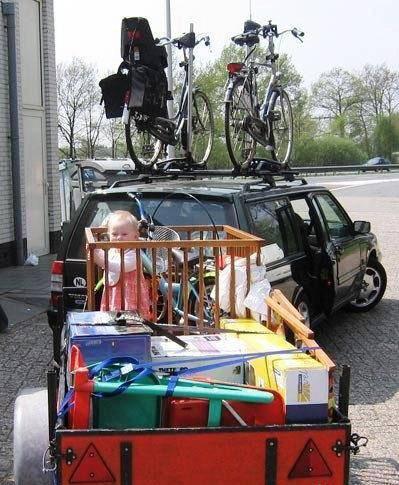 Ein holländisches Auto mit Anhänger, auf dem ein Kindergestell mit Baby steht.