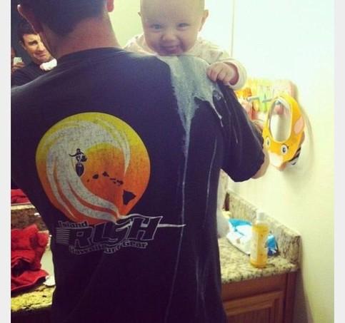 Ein Baby hat auf die Schulter seines Vaters gekotzt. Es lacht, als fände es das sehr lustig.