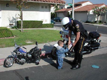 Ein Kind mit Kindermotorrad wird von einem Polizisten kontrolliert.