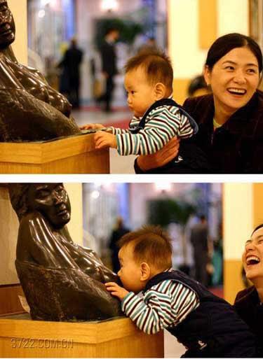 Ein Kind saugt an der Brust einer Statue.