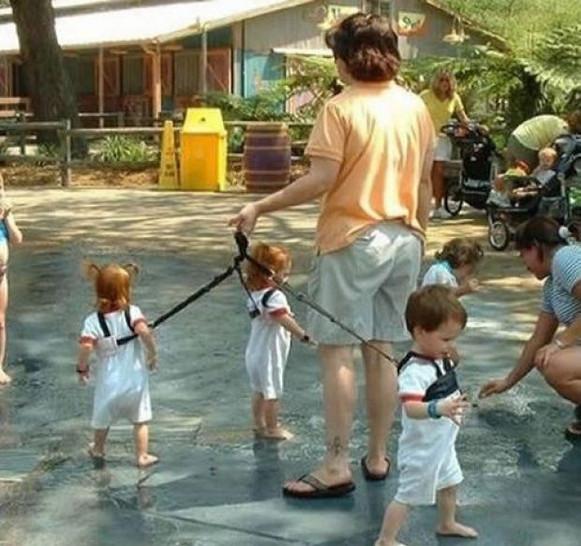 Ein Mann führt seine Kinder an einer Leine spazieren.
