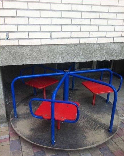 Ein Kinder-Dreh-Karussell ist unter einem Betonvorsprung aufgebaut. So kann kein Kind sitzend fahren.