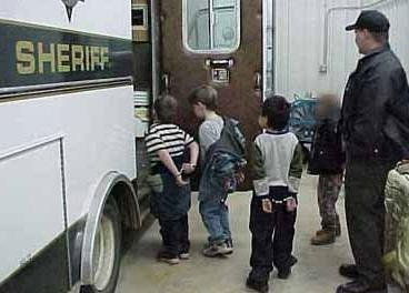 Kinder werden in Handschellen abgeführt.