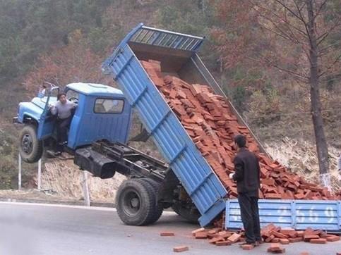 Ein LKW ist durch eine überladene Ladefläche nach hinten gekippt.