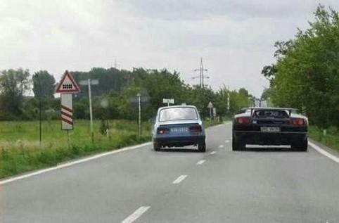 Ein Klapperauto überholt einen Sportwagen.