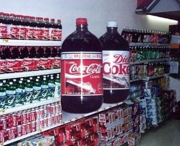Zwei riesengroße Flaschen Cola stehen in einem Geschäft.