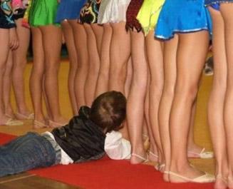 Ein kleiner Junge liegt hinter einer Reihe Mädchen und scheint ihnen unter den Rock zu linsen.