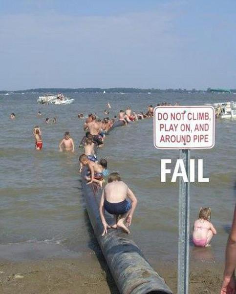 Auf einem Schild am Meer steht, dass es verboten ist, auf einer Röhre zu klettern und zu spielen. Die Röhre ist voll mit spielenden Kindern.