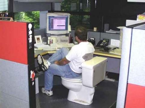 Ein Mann sitzt im Büro auf einem Klo.