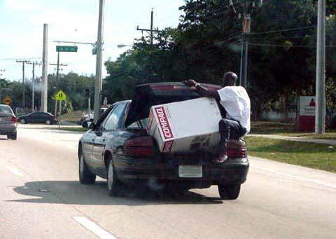 Ein Mann sitzt auf der Stoßstange eines fahrenden Autos und hält den Kofferraum zu.
