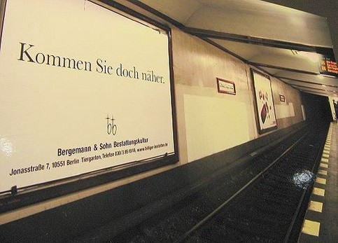 """Ein Werbeschild für Beerdigungen in einer U-Bahn-Station, auf dem steht """"Kommen Sie doch näher."""""""