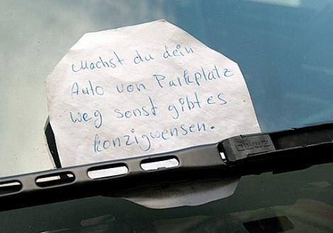 """Hinter dem Scheibenwischer eines Autos klemmt ein Zettel: """"Machst du dein Auto von Parkplatz weg sonst gibt es konsigwenzen."""""""