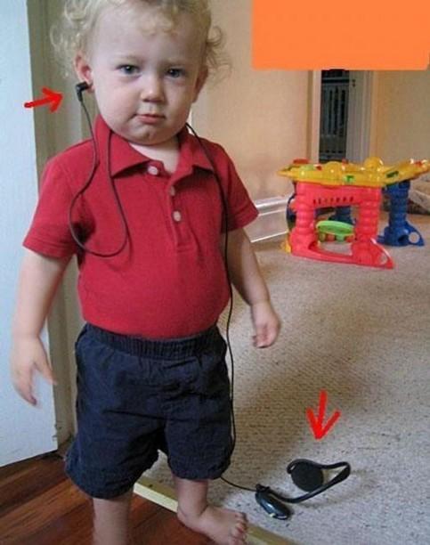 Ein Kind hat einen Kopfhörer auf, aber er hat sich den Stecker das Kabels ins Ohr gesteckt.