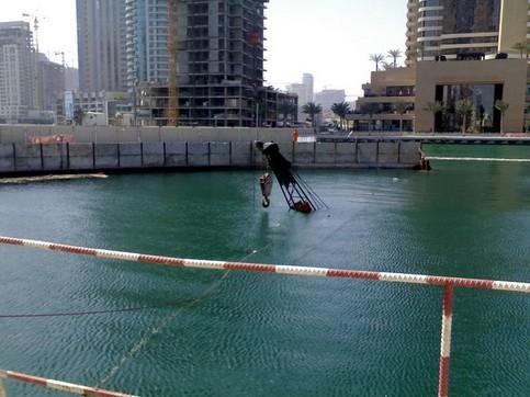 Ein Kran steht in einer Baustelle komplett unter Wasser, nur die Spitze schaut aus dem Wasser heraus.