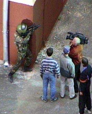 Ein Soldat steht hinter einer Ecke und wird von einer Kamera gefilmt.