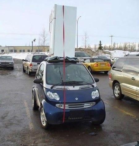 Ein Auto ist mit einem Kühlschrank auf dem Dach beladen, aber der Kühlschrank steht hochkant.