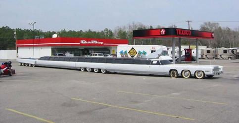 Eine extrem lange Limousine steht an einer Tankstelle.