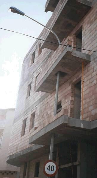 Ein Haus wird gebaut, die Balkone werden um eine Strassenlaterne herum gebaut.