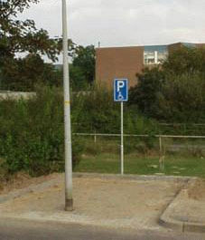 Ein Behindertenparkplatz, vor dem eine Laterne platziert ist.