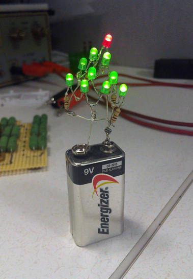An eine 9v-Blockbatterie wurden grüne LEDs in Form eines Weihnachtsbaums gelötet. An der Spitze des LED-Baumes thront eine rote LED.