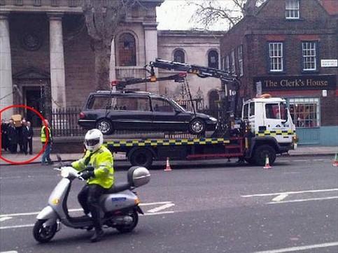 Ein vor einer Kirche parkender Leichenwagen wurde abgeschleppt, während der Sarg aus der Kirche herausgetragen wird.