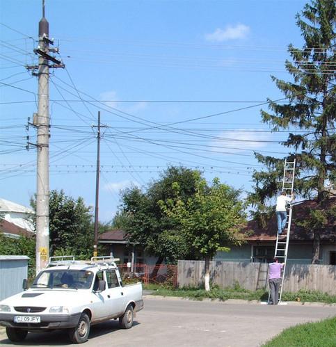 Ein Mann lehnt eine Leiter an eine Stromleitung an und klettert hinauf.
