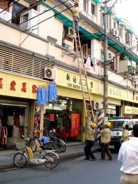 Ein Mann stemmt eine Leiter, auf der ein Arbeiter steht.