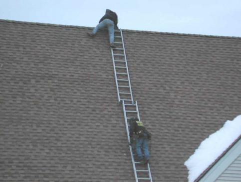 Ein Mann klettert auf ein Dach, indem er zwei Leitern aufeinander stellt.