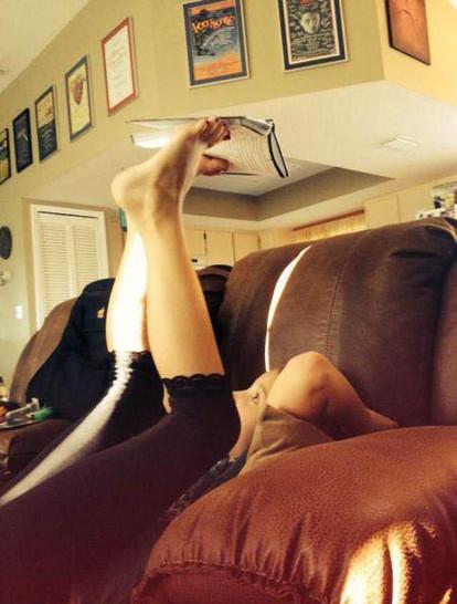 Ein Mädchen liegt auf einem Sofa und hält ein Buch mit ihren Füßen über ihren Kopf in die Höhe um zu lesen.