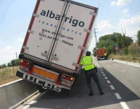 Ein LKW hängt gekippt auf einer Leitplanke aus Beton, ein Polizist versucht den LKW festzuhalten.