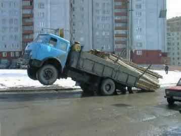 Ein überladener LKW, der vorne in der Luft hängt.