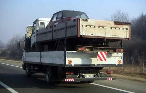 Ein LKW ist mit einem LKW beladen, der mit einem PKW beladen ist.