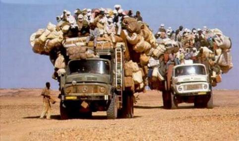 Zwei LKWs voll mit Menschen und Gepäck fahren durch die Wüste.