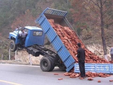 Ein LKW ist mit dem Führerhaus in die Lust gehoben, weil die Ladung Steine zu schwer ist.