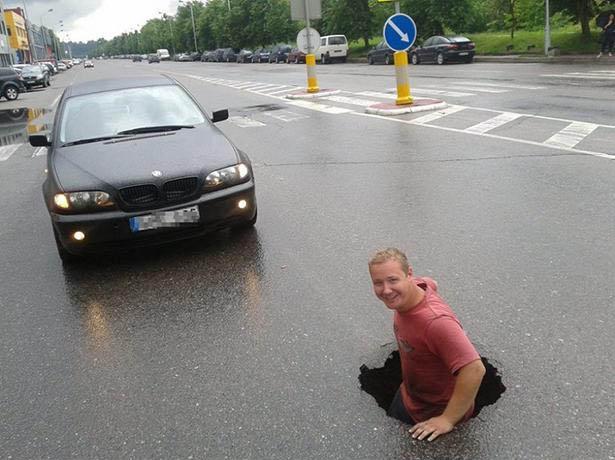 In einer Straße befindet sich ein so großes Loch, dass ein Mann hineingestiegen ist.