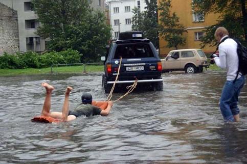 Ein Junge lässt sich im Hochwasser von einem Auto auf einer Luftmatratze ziehen.