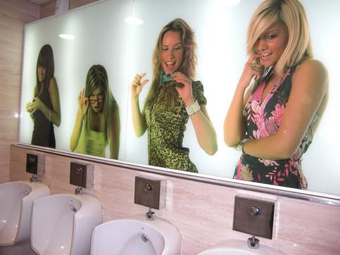 Über einer Reihe Pissoirs sind Bilder von Frauen angebracht, die nach unten schauen und lachen und mit dem Fernglas genau hinschauen.